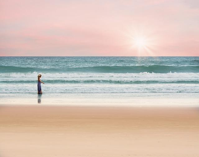 Kleines Mädchen alleine am Strand, Sonnenuntergang, rosa Himmel